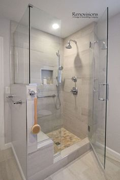 A completed Master Bathroom remodel by Renovisions. Walk-in Shower, shower seat, shower cubby, hand-held shower, glass shower door, mirrored medicine cabinets, fold out mirror, lighted medicine cabinets, double vanity, double sinks, grey, porcelain tile.
