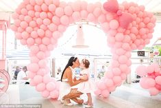 Doting mother: Terry knelt down to give her three-year-old a kiss as they stood between a ...