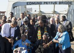US President Barack Obama(L) speaks to Amelia Boynton Robinson (2L), one of the original marchers,  after leading a walk across the Edmund Pettus Bridge to mark the 50th Anniversary of the Selma to Montgomery civil rights marches in Selma, Alabama, March 7, 2015. US President Barack Obama rallied a new generation of Americans to the spirit of the civil rights struggle, warning their march for freedom