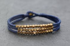 This is hand woven bracelet made with blue color cotton waxed cord weaved together with brass beads . Closure using brass bell  ♥ Bracelet measures