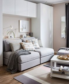 A GIF shows the transformation of a sofa to bed in this combination living room, guest bedroom, office and dining room - great ideas for our basement