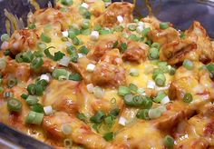 In the crock pot ~ Chicken breasts, enchilada sauce, taco seasoning, shredded cheese, and green onions, then served up in soft tortillas with rice