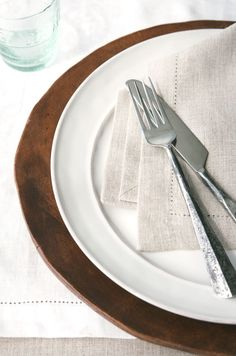 White + Brown stacked plates with neutral linen napkin.
