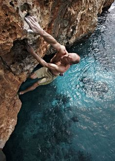 """DWS psicobloc, which translates into """"psycho bouldering"""".In this sport, climbers forgo ropes and harnesses, using the water beneath their seaside routes as protection. BUCKET LIST"""