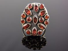 Made with faceted marquis and round garnet gemstones, sterling silver metal and half-round wire. Size 6.5