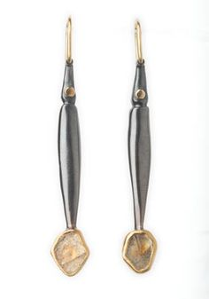 "Alison B. Antelman, ""Pods,"" Earrings, hand fabricated, fold formed hollow forms in oxidized sterling silver, with 18k & 22k gold, and rough Montana sapphire. 2"" in length."