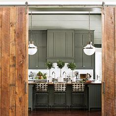 The Kitchen | Taken from an early-1900s Tennessee barn, the knotty boards of the custom sliding barn doors add rustic texture against the smooth painted walls. | #SLIdeaHouse | SouthernLiving.com
