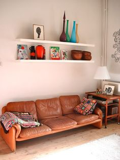 Vintage leather couch and string art on the wall at Kathleen Mine's home in Belgium
