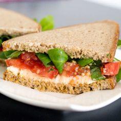 Caprese Salad Sandwiches    1 mozzarella ball, sliced     1 tomato, thinly sliced     handful basil, slivered     handful salad greens     ½ tablespoon basil pesto     ½ tablespoon sun dried tomato pesto