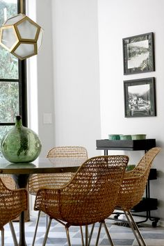 Wicker dining space with glass green vase and hexagonal chandelier