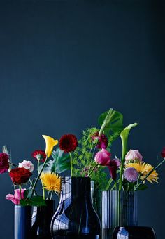 Colorfull flowers in different shaped vases.