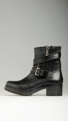 Zippered straps detailing black leather ankle boots featuring round toe, visible stitching, side zip fastening, 1.9'' heel, vibram rubber sole, 100% leather.