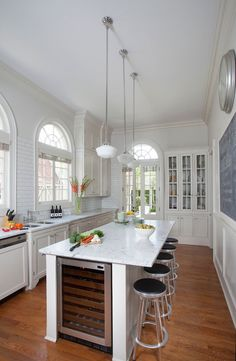 Long kitchen design boasts schoolhouse pendants illuminating long island topped with white marble ...