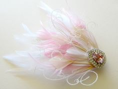 Wedding Hair Accessories Feather Fascinator by parfaitplumes, $35.00  This feminine feather hair piece starts with a background of white Nagoire feathers. The overlay of blush pink and white coque feathers give the piece movement This beautiful piece is accented with ivory curled peacock herl wisps. The central jewel is encrusted with clear Czech rhinestones and a large central pink teardrop rhinestone.  #weddings#hair#accessory#featherfascinator#gatsby#1920s