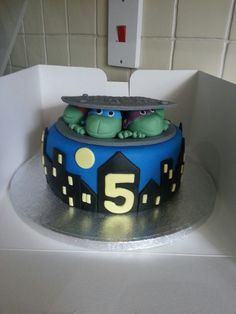 Ninja Turtle cake. Ninjas coming out of a man hole at night over the city.