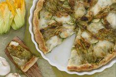 La torta di zucchine e i suoi fiori è un gustoso e nutriente secondo piatto a base di sfoglia ripiena di zucchine, fiori di zucca e mozzarella.