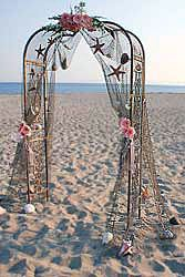 mermaids dream... fish net with shells and flowers on a garden trellis.