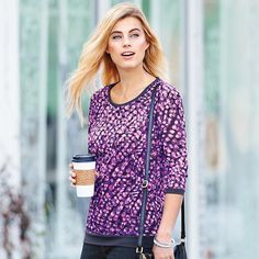 This fresh take on the comfy sweatshirt has a cool purple print and lightweight fabric and a relaxed fit. Features darker purple ribbed knit trim at arms, neck and hemline. · Body: 100% Polyester · Trim: 60% Cotton, 35% Polyester, 5% Spandex Turn garment inside out. Machine wash cold on gentle cycle with similiar colors; do not use chlorine bleach, use only non-chlorine bleach, if needed. Tumble dry low; cool iron as needed. Imported