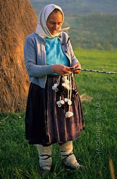 [ROMANIA.MARAMURES 23.650] 'Shepherd near Breb.'  	While keeping an eye on her sheep this shepherd has attached her braiding work to a fence. Photo Mick Palarczyk.