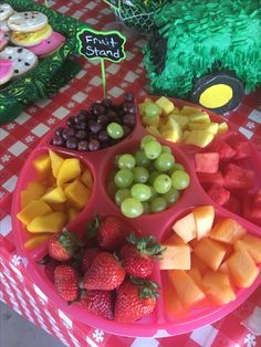 "Farm 2nd Birthday Party snack table -  ""Fruit Stand""  lfruit platter in red Tupperware divided server with green chalkboard sign. Tractor piñata as table decoration with red checkered tablecloth. Tablecloth, chalkboard signs from Hobby Lobby, tractor piñata from shindigz.com, handkerchiefs from Tractor Supply"