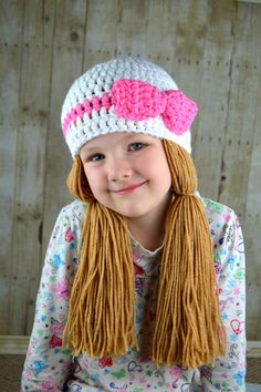 White and Pink Doll Pigtail Wig  • Handmade with 100% acrylic yarn • Pigtail beanie • Yarn doubled for extra warmth and durability • SUPER comfortable • Doubles as a costume piece or a winter beanie  Yumbabys cure for pre-premature baldness!!! My little girl loves this style of hat. She is quite a diva and enjoys dancing around the house flipping her long princess hair. This hat is thick, warm and durable. The beanie is white and pink; hand crocheted with high-quality yarn. The hair is…