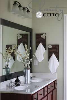pretty bathroom like the towel holders and also the flowers and tin vase