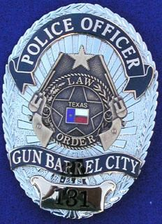 """This is the Gun Barrel City Texas Police Officer badge. The logo has Texas' state flag placed in the middle of the badge, inside a 5 pointed star which is encircled with a circle and wreath with the inscription of """"Law Order"""" then 2 pistols and another star which is smaller than the other one then a banner on top with the word """"Police Officer""""."""