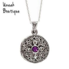 Round Amethyst Marcasite Locket. This pretty marcasite locket is set with a deep purple Siberian Amethyst in the centre of the locket which is surrounded by an intricate mix of openwork swirl shapes, delicate silver beading and etching all set with gleaming marcasite gems.