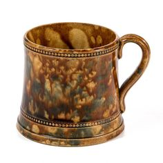 BENNINGTON-ATTRIBUTED FLINT ENAMEL POTTERY MUG,  molded, with a dotted, embossed pattern at rim and base, Rockingham-style glaze with splashes of green enamel. Unmarked. Bennington Pottery, Bennington, Vermont.