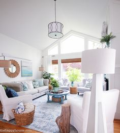 Coastal and beachy blue & green summer living room tour featuring of pops of blue, green, and natural rustic textures against a white and neutral backdrop.