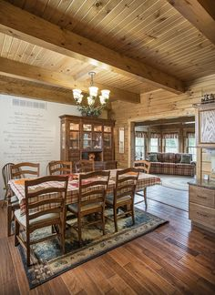 The dining room of this Hochstetler Log Home showcases beautiful exposed beams and hardwood floor. #loghomes #logcabins #exposedbeams #loghome #logcabin