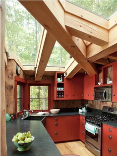 """How lovely would it be to cook in this kitchen, with the lake and a grove of pine trees out your window and plenty of light streaming through the skylights? Not to mention those beautiful deep-red cabinets and wood all around you: antique oak floors, recycled barn-board walls, pine ceiling planks. The owners say the house is """"magic,"""" and we believe it."""