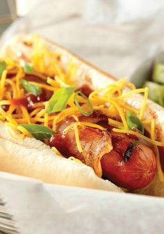 Memphis-Style BBQ Dogs -- Wrapped in bacon and topped with BBQ sauce, green onions and shredded cheese, this hot dog recipe has a delicious down-home appeal.