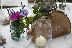 The table decor was simple and low-cost. Found mason jars combined with garden flowers, and some nice candles from Michael's really created a striking combo.  #masonjars #wedding #diy