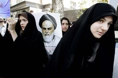 MUSLIM WOMEN, UNITE: A protester held a poster of the late Ayatollah Khomeini during a demonstration Thursday at the Swiss Embassy in Tehran, Iran, against a film made in the U.S. and posted online that ridiculed the Prophet Muhammad. (Vahid Salemi/Associated Press)