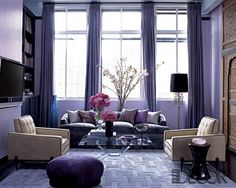 A purple living room, dressed into a Lila suave light. There is a comfortable purple sofa in front of the window, many pillows in different purple nuances on ii. Two vanilla armchairs make a contrast with the purple of the whole room. A purple round chair on the floor, some suave flowers on a vase and the purple curtains invite you to lay on the sofa and dream of spring.