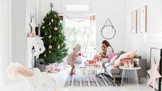 A arquiteta Lee Talbot vive com seu marido e três filhos em uma casa na costa sul da Austrália. Os interiores foram pintados de branco, dando um tom moderno e claro ao lar. No Natal, os ambientes ganham vida. Na sala de estar, o pinheiro é o grande destaque e foi enfeitado com algumas penas, ornamentos de papel (origamis) e estrelas. Tons de rosa nos papéis de presente e outros enfeites dão uma atmosfera alegre. E as almofadas complementam com cores suaves o cômodo. #natal #decor