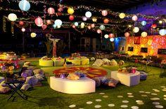 A decoração despojada da Festa Luau: muitas luminárias, almofadas, pufes e cores