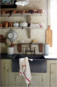 The way the pots and pans are stored and organized, nice. Love the earthy rustic feeling. More good ideas for my small kitchen.