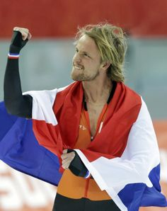 Michel Mulder from the Netherlands holds his national flag and celebrates winning gold in the men's 500-meter speedskating race at the Adler...