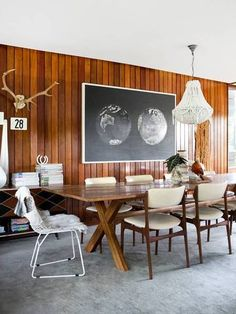 Love how this modern dining room  makes dark wood paneling feel modern.