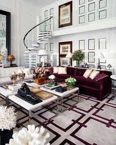 Double-height ceilings, a crazy staircase to an almost invisible 2nd floor door, the burgandy velvet #sofa atop a geometric rug, huge pieces of coral on pedestals, exquisite silk stripes on the round, skirted table, four chrome-legged coffee tables, etc., etc. combine to make one of my all-time favorite living rooms. (By Pablo Paniagua, as seen in Nuevo Estilo revista de decoración)