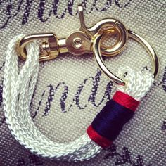 Multi strand white rope bracelet with navy and red detail.