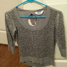 Quarter sleeve sweater! Super cute grey high low sweater with sequins on the front and a bow on the back with a little opening behind the bow! Has been worn (one of my favorites) but its time to give it to a new home! On the top right by the sleeve(third pic), but is not really noticeable and is fixable if you sew on a couple of sequins.the bow on the back has a little snag in the thread(last pic) but also not noticeable at all unless someone is looking super close at your back! Is a size…