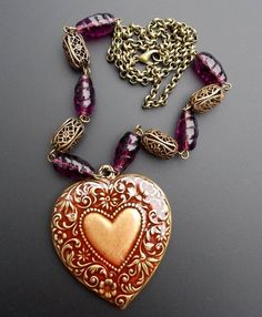 This necklace features a brass heart that has purple cold enameling on one side and tissue decoupage of script writing on the other side.  Brass