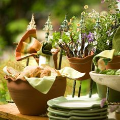 Stick with a simple decorating theme to create a cohesive outdoor buffet spread. Here, we used garden elements, such as large pots and birdbaths, for servingware and stashed silverware in a small ceramic pot secured to a wrought-iron frame adorned with wildflowers.
