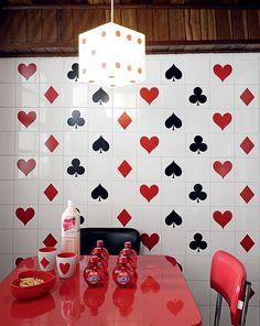 Inspirada nos anos 1950, a cozinha de azulejos brancos recebeu adesivos de naipes de cartas. A ideia surgiu pois o imóvel alugado. Casa da estilista Patricia Grejanin