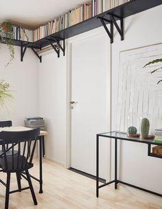 Liten spiseplass med spisebord og skrivebord med lange, tynne ben samt bokhyller til høyt oppe under taket.