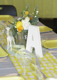 yellow baby shower. Letter, flowers, toy animal