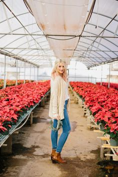 Greenhouse winter boho photoshoot surrounded by poinsettias. ASOS jeans, Chicstyle Cardigan, Forever 21 booties and a gorgeous winter hair crown.  Outfit from www.theredclosetdiary.com